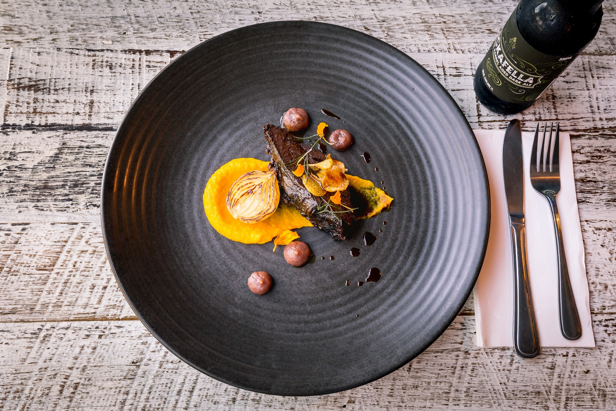 bellbird dining_meat dish on a plate with wine and cutlery on the right side