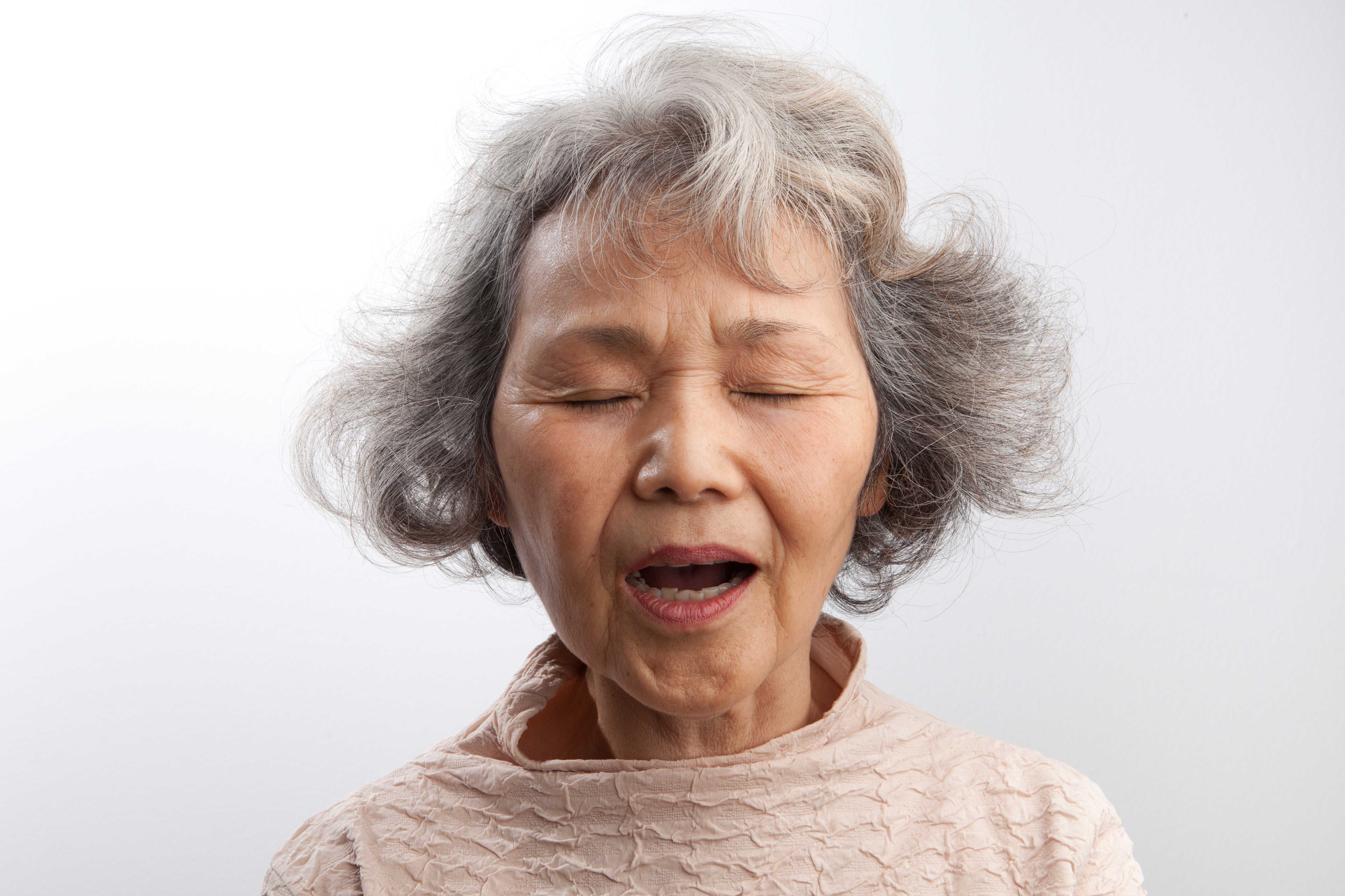 Older Asian woman with short gray hair with eyes closed and lips open